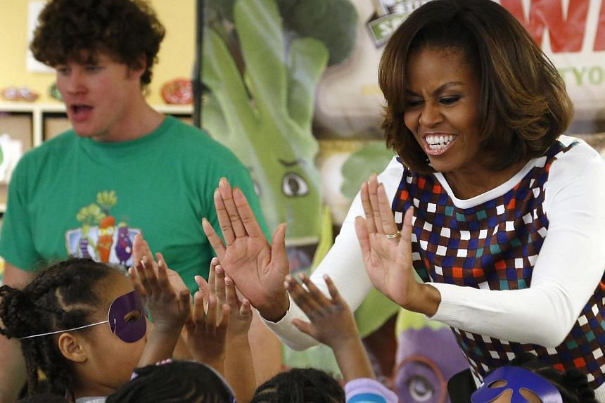 US first lady Michelle Obama gives out high fives after learning a dance and exercise with children at a La Petite Academy chid care center in Bowie, Maryland, on Feb 27, 2014. She will make a first visit to China between March 19 and 26 and fin