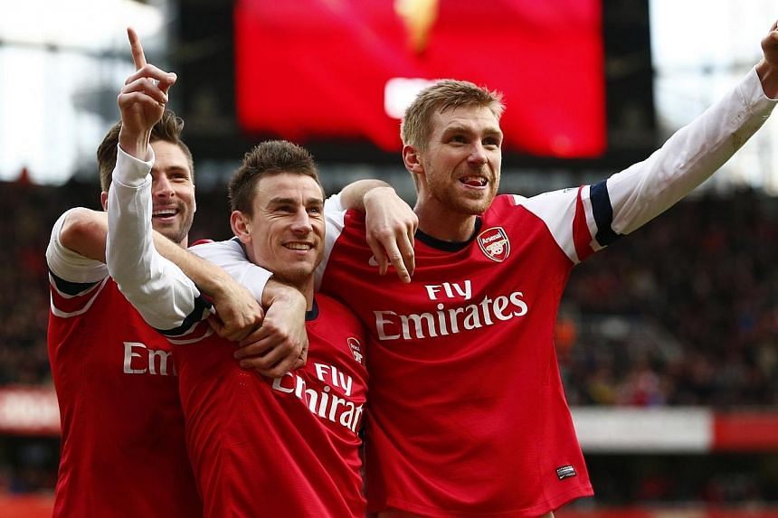 Arsenal's Laurent Koscielny (centre) celebrates his goal against Sunderland with Olivier Giroud (left) and Per Mertesacker (right) during their English Premier League soccer match at the Emirates Stadium in London, Feb 22, 2014. German centre-back Pe