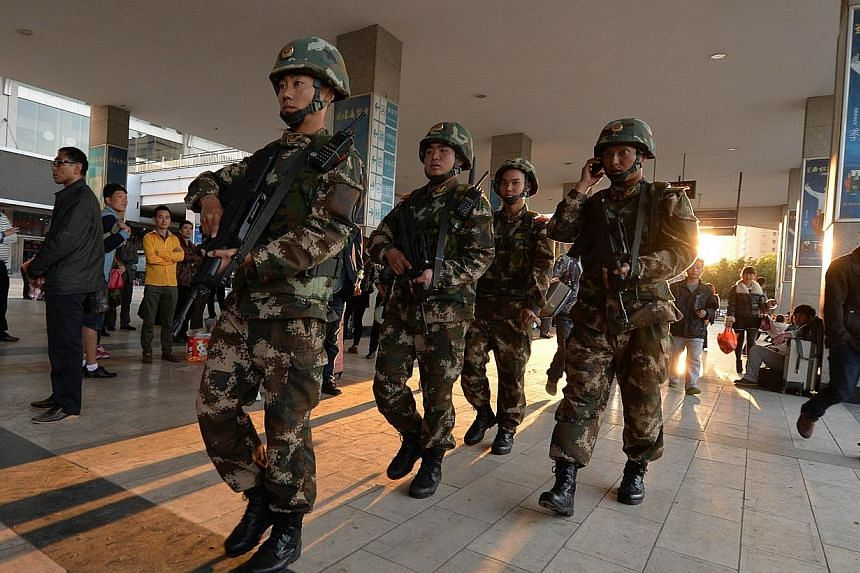 Chinese paramilitary police patrol outside the scene of the terror attack at the main train station in Kunming, Yunnan Province, on March 3, 2014. -- PHOTO: AFP