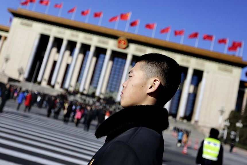 A soldier in plain clothes from the Chinese People's Liberation Army (PLA) stands guard in front of the Great Hall of the People, the venue of the annual session of China's parliament, the National People's Congress (NPC), in Beijing March 4, 2014. C