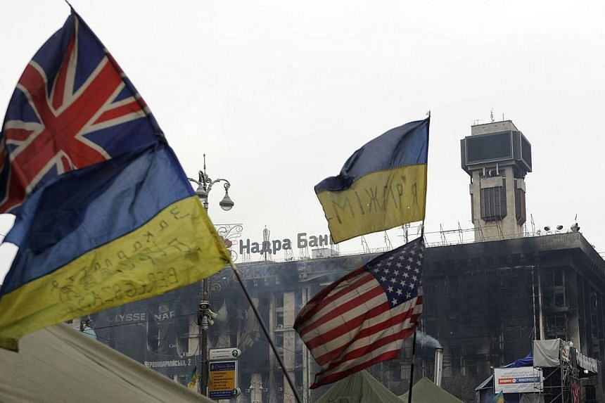 The flags of Ukraine, US and the Great Britaine flutter on Independence Square in Kiev on Feb 27, 2014.Britain opposes trade or financial sanctions on Russia over its intervention in Ukraine, media reports said on Tuesday, March 4, 2014, citing