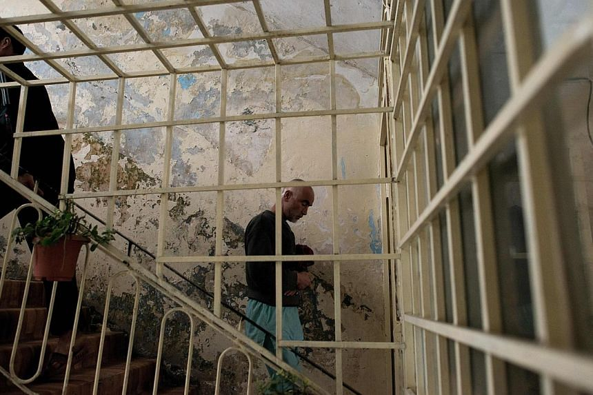 This picture taken on February 20, 2014, shows patients walking in the staircase at the Jangalak hospital in Kabul. The Jangalak hospital is a government runned hospital with a capacity of 300 beds, that receives drug users for a 45 days treatment pe
