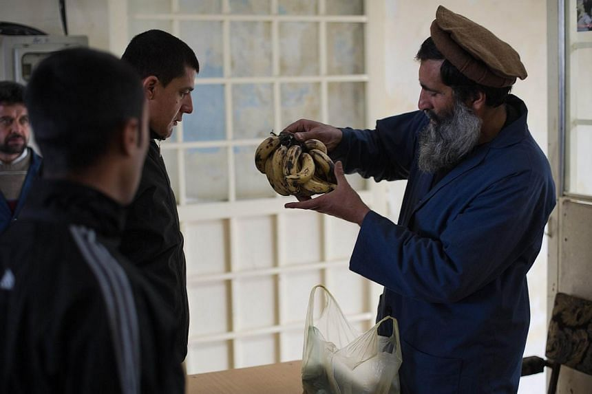 This picture taken on February 23, 2014, shows two patients waiting while a security guard checks their bag of bananas for any hidden things that are not allowed, delivered to them by relatives at the Jangalak hospital in Kabul. The Jangalak hospital