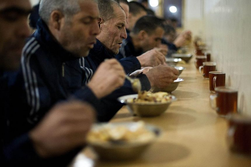 This picture taken on February 27, 2014 shows patients eating dinner at the Jangalak hospital in Kabul. The Jangalak hospital is a government runned hospital with a capacity of 300 beds, that receives drug users for a 45 days treatment period, to cur