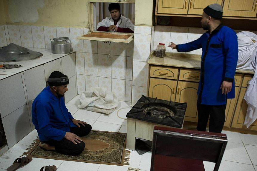 This picture taken on February 27, 2014 shows a cook praying before to serve the dinner to patients (not seen) at the Jangalak hospital in Kabul. The Jangalak hospital is a government runned hospital with a capacity of 300 beds, that receives drug us