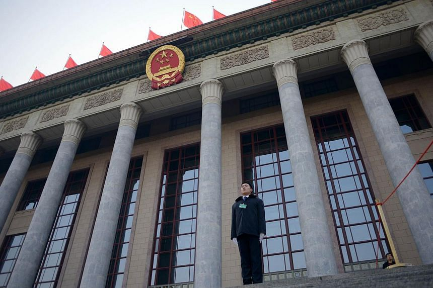 A security guard standing in front of The Great Hall of the People before the upcoming opening sessions of the Chinese People's Political Consultative Conference (CPPCC) and the National People's Congress (NPC) in Beijing on March 2, 2014. -- PHOTO: