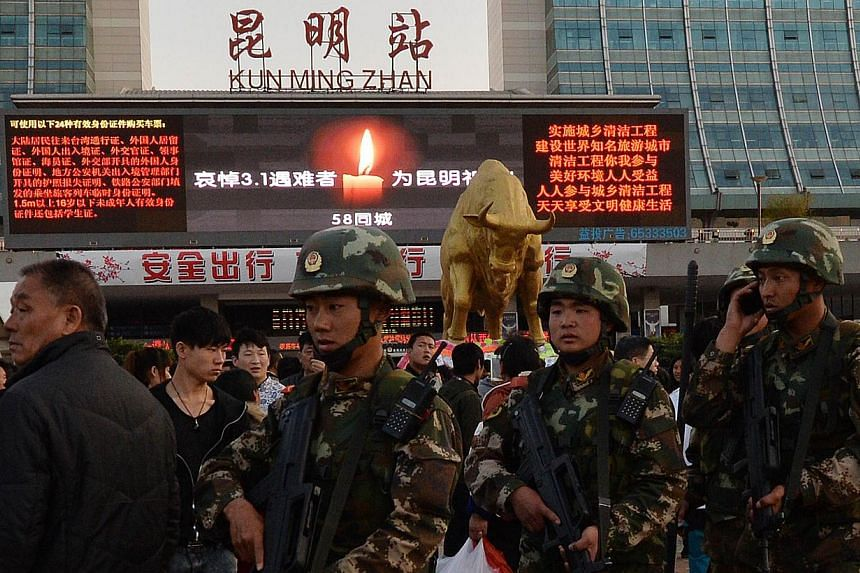 Chinese paramilitary police patrol outside the scene of the attack at the main train station in Kunming, Yunnan Province, on March 3, 2014. -- PHOTO: AFP