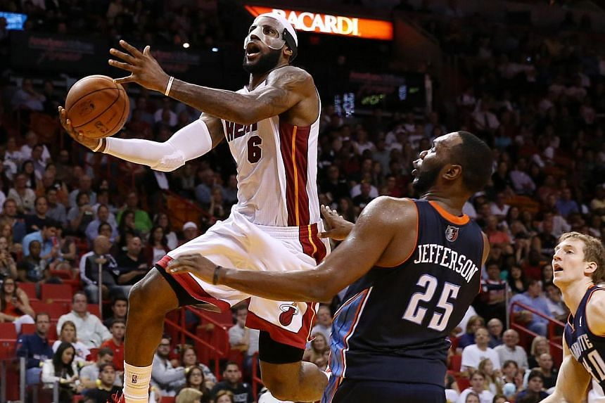 Miami Heat small forward LeBron James (6) drives to the basket past Charlotte Bobcats centre Al Jefferson (25) in the second half at American Airlines Arena on Mar 3, 2014. -- PHOTO: REUTERS