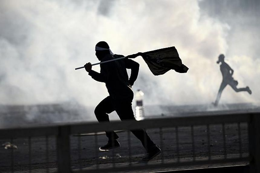 Bahraini protesters run for cover from tear gas fired by riot police during clashes on March 3, 2014 in the village of Daih, west of the capital Manama, following a rally to protest against the death of Jaffer al-Durazi who died in hospital last week