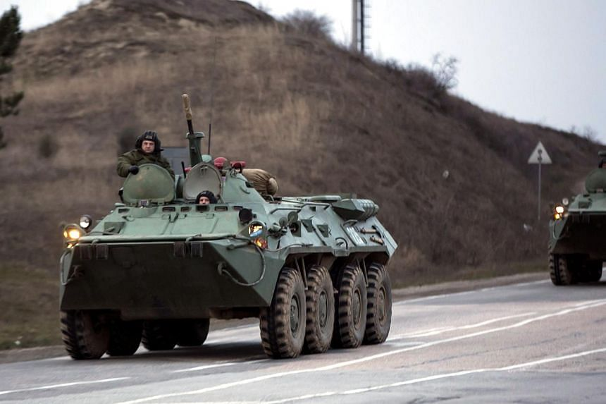 """Russian military armoured personnel carriers (APC) drive on the road from Sevastopol to Simferopol on March 4, 2014.Russian President Vladimir Putin on Tuesday denied that Russian forces were operating in Crimea, saying that only """"local forces"""
