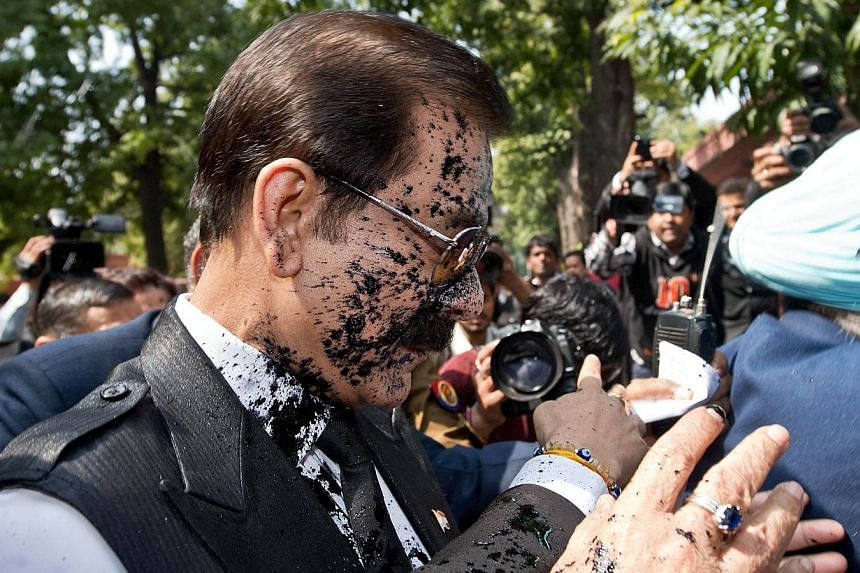India's Sahara group chairman Subrata Roy's face is covered in black ink after a protester attacked him as he arrives at the Supreme Court in New Delhi on March 4, 2014.The court issued the order after Roy's lawyers said he could not appear in
