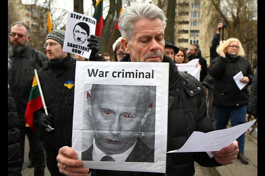 Demonstrators hold posters featuring Russian President Vladimir Putin as German nazi dictator Adolf Hitler and as a devil during a protest against Russia's intervention in Ukraine in front of the Russian embassy in Vilnius, on March 3, 2014. Put