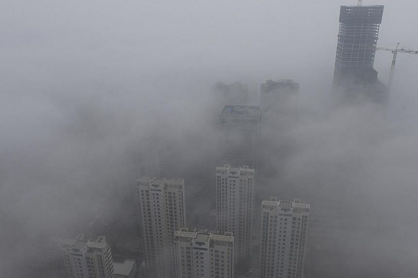 Buildings are seen shrouded in heavy haze at Qingdao development zone, Shandong province, on Feb 25. The Chinese government is reviewing proposals for environmental levies and a nation-wide property tax, an official said on Tuesday. -- FILE PHOTO:&nb