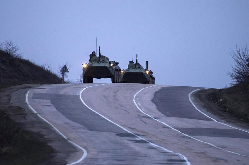 Russian military armoured personnel carriers (APC) drive on the road from Sevastopol to Simferopol on March 4, 2014.Fears of an assault by Russian forces on Ukrainian military bases that were surrounded in Crimea did not materialise overnight,