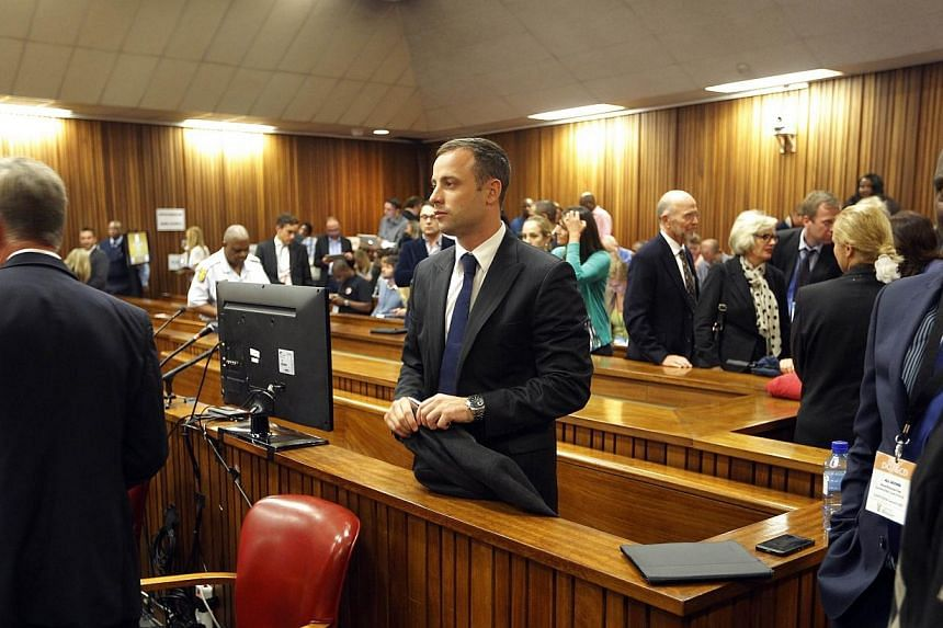 South African Paralympic athlete Oscar Pistorius (centre), accused of murdering his girlfriend, looks on during a break on the second day of his trial at the North Gauteng High Court in Pretoria, South Africa, on Tuesday Mar 4, 2014. -- PHOTO: AFP