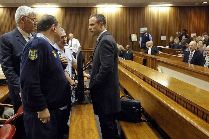 South African Paralympic athlete Oscar Pistorius (centre), accused of murdering his girlfriend, speaks to his defense team after arriving at the North Gauteng High Court in Pretoria, South Africa, for the second day of his trial on Tuesday, Mar 4, 20