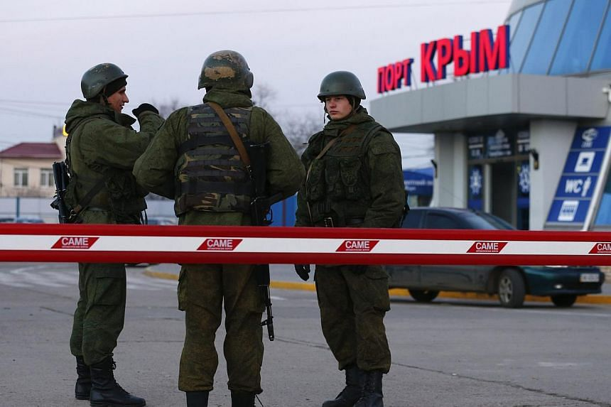 Armed men, believed to be Russian soldiers, stand outside the civilian port in the Crimean town of Kerch on March 3, 2014. The United States has suspended defence cooperation with Russia because of Moscow's military intervention in Ukraine, the Penta