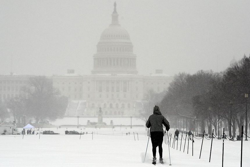 A man uses skis to make his way on the national mall during a snow storm in Washington, DC, on March 3, 2014. -- PHOTO: AFP