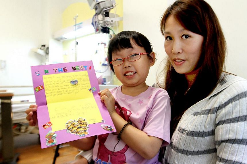 """Phyllis with her mother, Madam Joanne Ng, in hospital, where she was preparing for surgery. She is holding a card she made for her donor to thank him for giving her part of his """"precious liver"""". -- ST PHOTO: LAU FOOK KONG"""