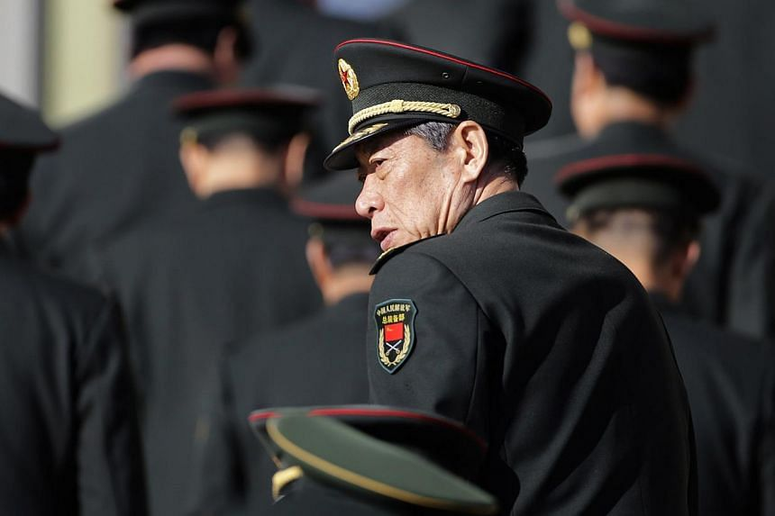 A military delegate from the Chinese People's Liberation Army (PLA) looks back as he and others arrive at the Great Hall of the People for a plenary meeting of the National People's Congress (NPC), China's parliament, in Beijing on March 4, 2014. Chi