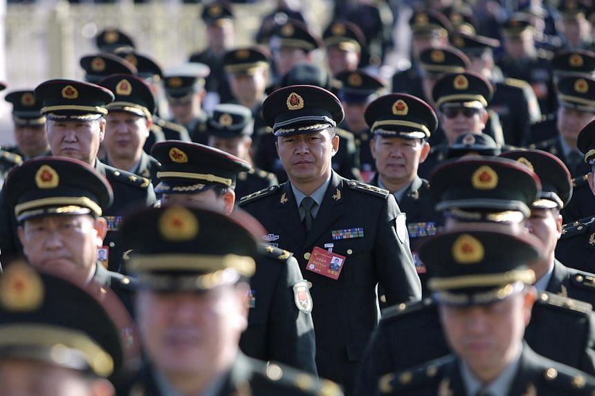 Military delegates from the Chinese People's Liberation Army (PLA) walk towards the Great Hall of the People for a plenary meeting of the National People's Congress (NPC), China's parliament, in Beijing March 4, 2014. -- PHOTO: REUTERS