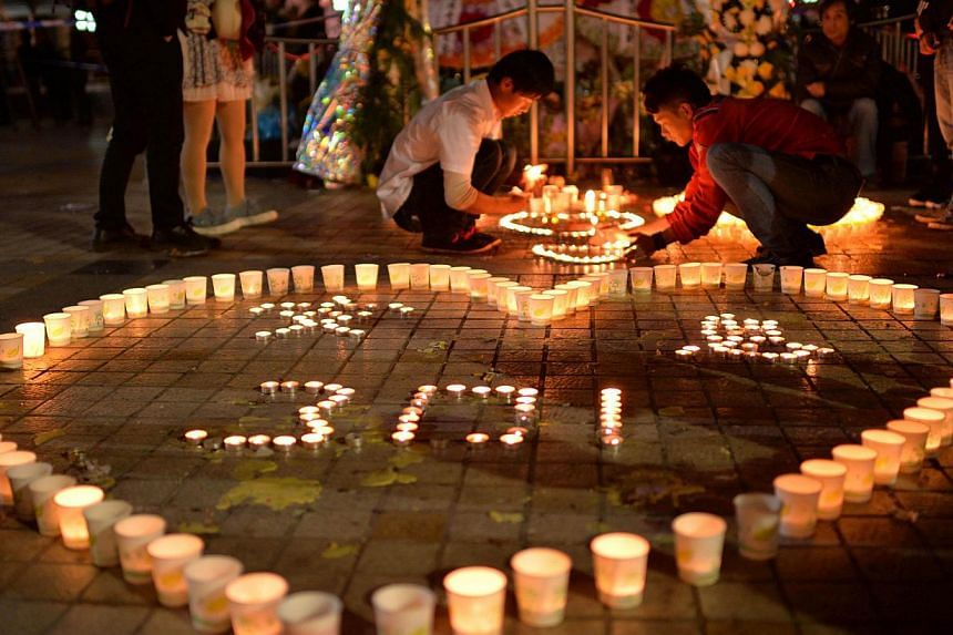 This picture taken on March 2, 2014 shows Chinese mourners lighting candles at the scene of the terror attack at the main train station in Kunming, south-west China's Yunnan province. Residents in several major cities across China have been unnerved
