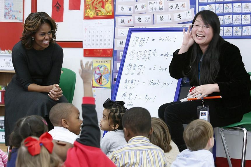 US Ffirst Lady Michelle Obama participates in a language class with teacher Crystal Chen for pre-school students at the Washington Yu Ying Public Charter School ahead of her upcoming trip to China, in Washington March 4, 2014. -- PHOTO: REUTERS