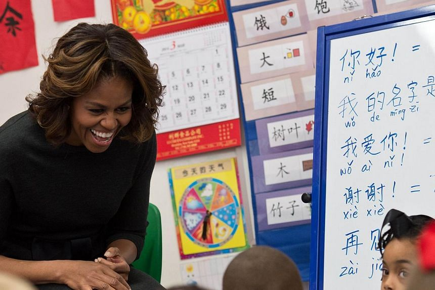 US First Lady Michelle Obama laughs with students as she learns some basic Mandarin at Washington Yu Ying Public Charter School, a Chinese-immersion, International Baccalaureate, elementary school, in Washington on March 4, 2014. She travels to China
