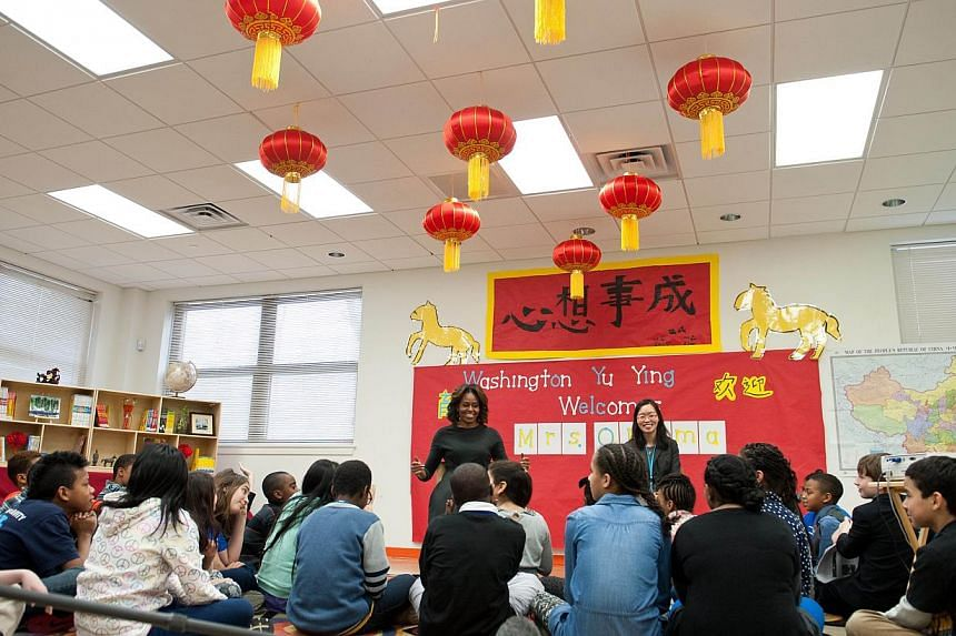 US First Lady Michelle Obama speaks with a group of sixth graders who recently visited China at Washington Yu Ying Public Charter School, a Chinese-immersion, International Baccalaureate, elementary school, in Washington on March 4, 2014. -- PHOTO:&n