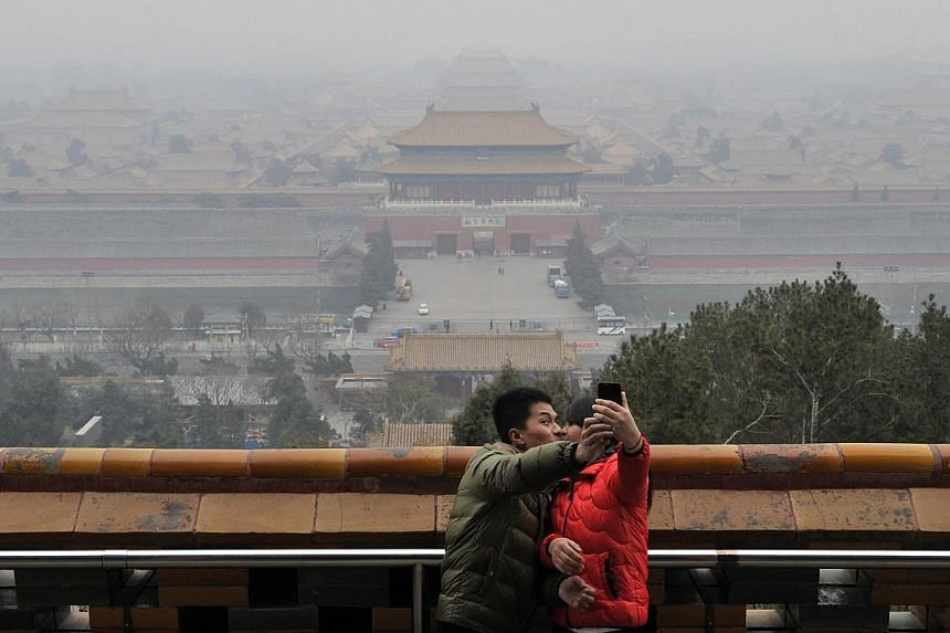 A couple taking a picture of themselves in front of the Forbidden City through thick haze on the top of Jingshan Park in Beijing, March 3, 2014. -- PHOTO: REUTERS