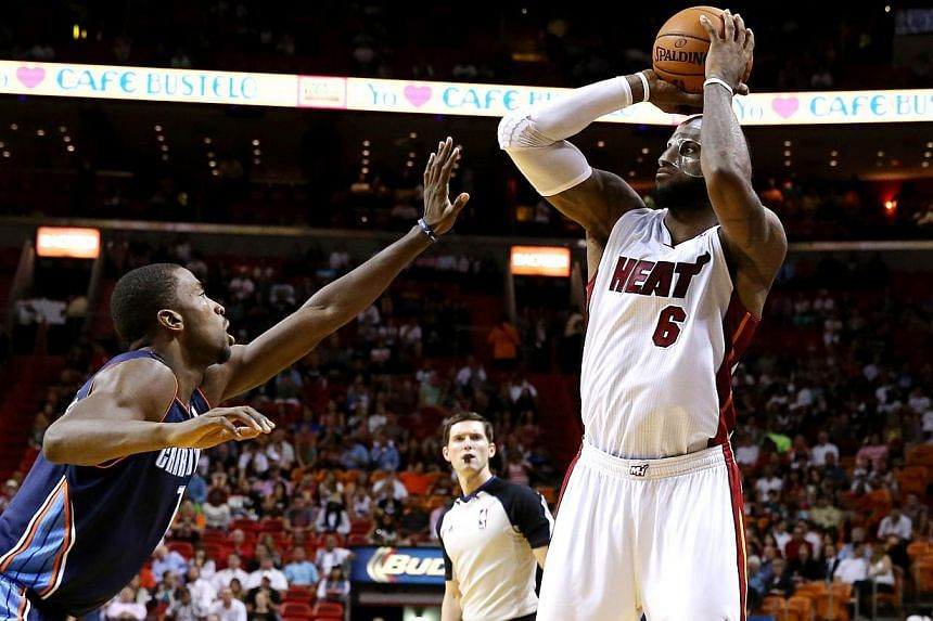 Miami Heat small forward LeBron James (6) makes a shot over Charlotte Bobcats point guard Kemba Walker (15) in the second half at American Airlines Arena. -- PHOTO: REUTERS