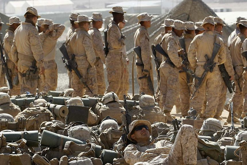 United States soldiers wait to start the multilateral training Eager Lion Exercise with their Jordanian counterparts, at Al Quweira near Aqaba city, 290km south of Amman on June 16, 2013. The Pentagon has proposed only a slight decrease in war fundin