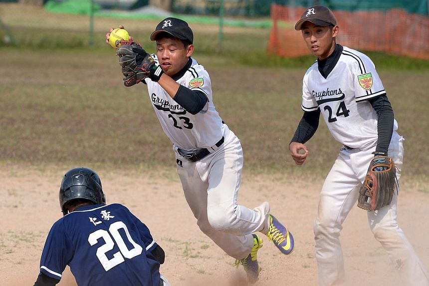 Raffles Institution's B Division boys' softball team (in white) retained their title after a thrilling battle against Catholic High School, winning 9-8 at the Kallang Field yesterday afternoon. -- ST PHOTO:LIM SIN THAI