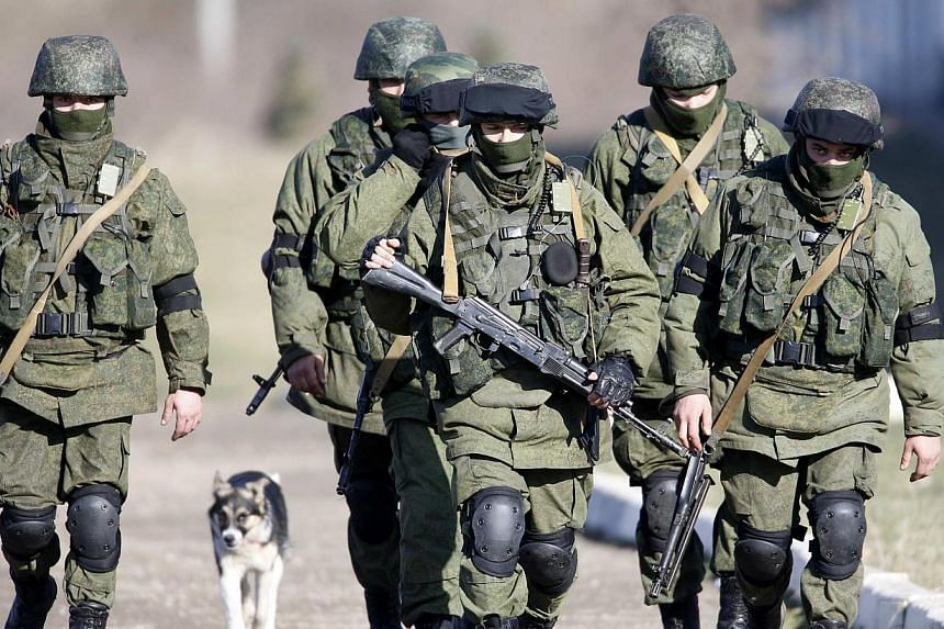 Armed men believed to be Russian servicemen march outside a Ukrainian military base in the village of Perevalnoye, outside Simferopol, on March 5, 2014.Ukraine's interim government and France on Wednesday played down the prospect of a full-blow