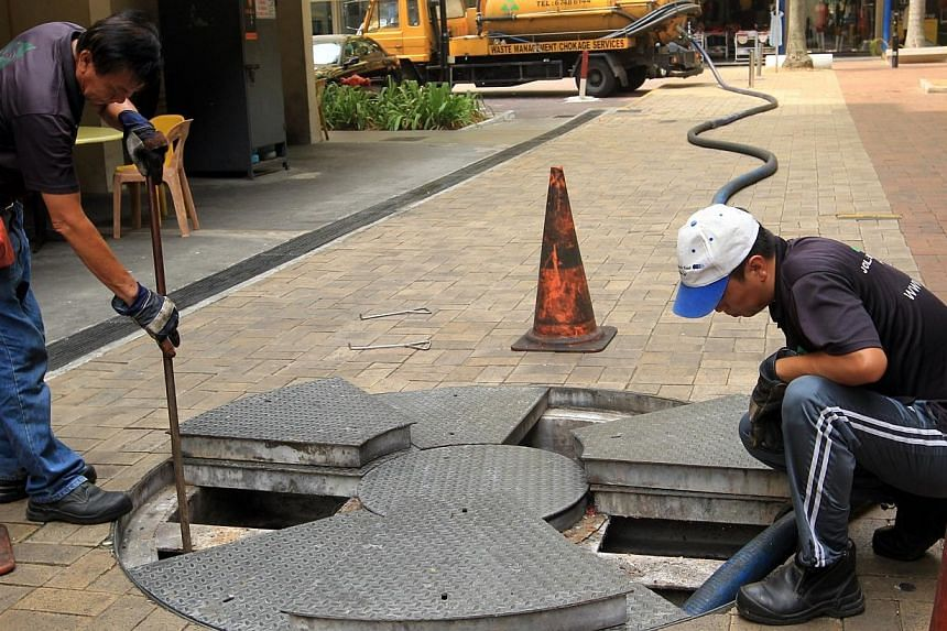 Staff from National Environment Agency-licensed general waste collector J.O.L Environmental at the manhole at Block 73A, Lorong 4 Toa Payoh at 2pmon Monday, after the two men who were seen extracting used cooking oil in the morning disappeared.