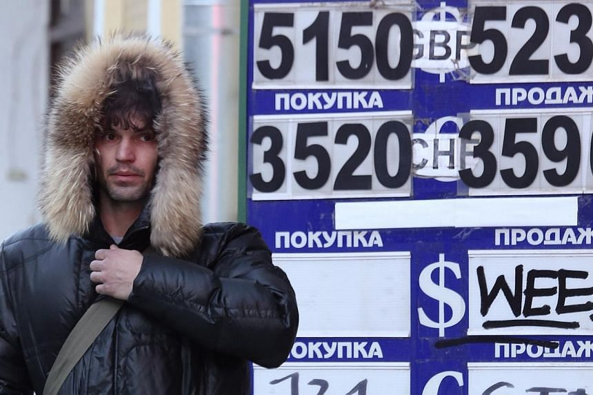 A man walks past a currency exchange board showing rouble exchange rates in Moscow on Jan 29, 2014.Russia sold a record US$11.3 billion (S$14.3 billion) in foreign currency to support the ruble on March 3, when the ruble came under unprecedente