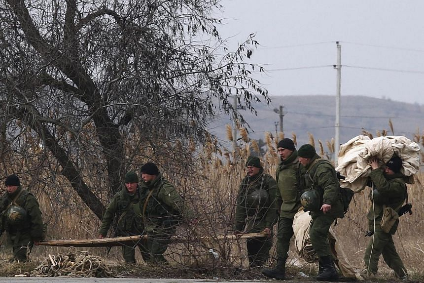 """Armed men, believed to be Russian servicemen, carry equipment as they set up a temporary camp at the terminal of the ferry port in the Crimean town of Kerch on March 4, 2014.Russia's deployment of forces in the Crimea region is having an """"extre"""