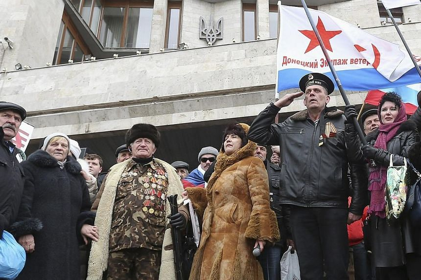 Pro-Russian demonstrators hold a rally outside the regional government building in Donetsk, March 3, 2014.Ukraine raised its flag over the government headquarters in the eastern city of Donetsk on Wednesday, where a Russian flag had stood since