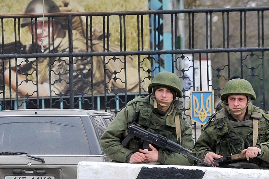 Members of the Russian forces stand guard at the gateway of the Ukrainian unit in the small Crimean city of Kerch on Wednesday, March 4, 2014.Russian forces have seized part of a Ukrainian missile defence unit in the disputed Black Sea peninsul