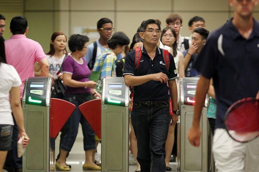 Commuters passing through the gantries at Toa Payoh MRT station on March 5, 2013. From Thursday, March 6, commuters will be able to apply for a new travel card that caps monthly spending on train and bus fares to $120. -- ST FILE PHOTO: NEO XIAO