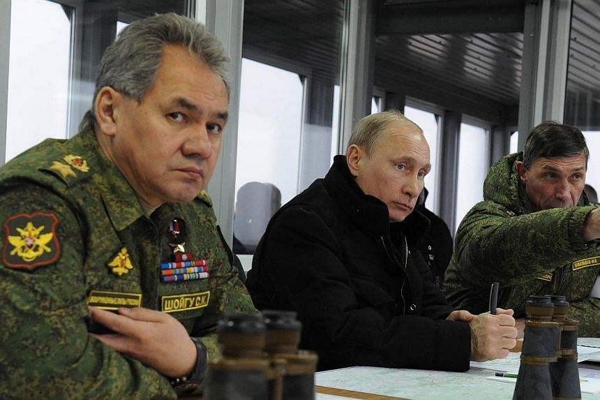 """Russian Defence Minister Sergei Shoigu (left) said on Wednesday, Mar 5, 2014, that photographs from Crimea of military vehicles with Russian number plates and video of an armed man claiming he is Russian were a """"provocation"""" and """"nonsense"""". -- PHOTO:"""