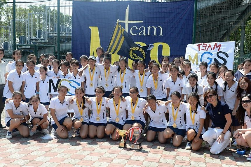 Methodist Girls' School's (MGS) team with their trophy. MGS continued their dominance in the Schools National B Division girls' tennis championships, clinching their fourth straight title with a 4-1 victory over rivals Raffles Girls School on Wednesd