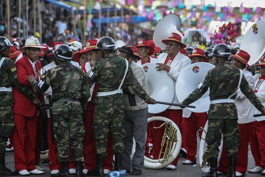 Musicians from the Poopo Banda speak with soldiers after a footbridge collapsed during the Carnival parade in Oruro, Bolivia, on March 1, 2014. -- FILE PHOTO: REUTERS