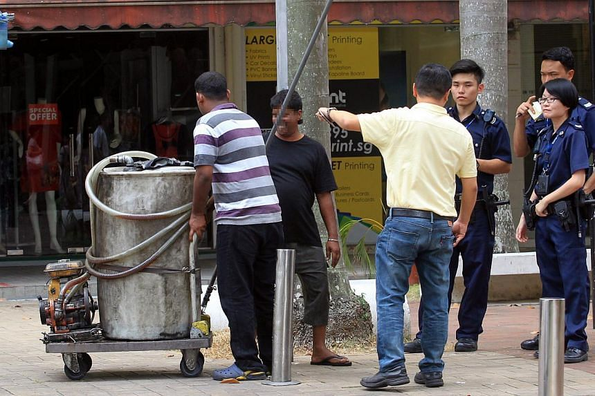 (Above) An oil tank said to have been used in the illegal siphoning of waste oil from a grease trap at Lorong 4 Toa Payoh being removed. (Below) Employees from licensed waste collection company J.O.L. Environmental collecting waste oil from a grease
