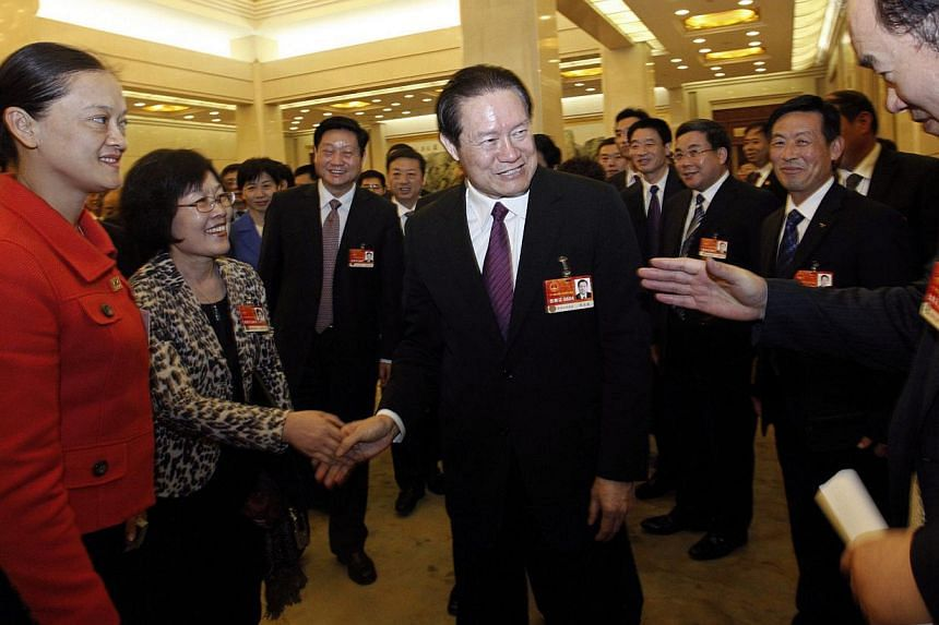 In this March 12, 2011 file photo, Chinese former Politburo Standing Committee Member Zhou Yongkang (C) shakes hands with delegates as he attends a group discussion of Shaanxi Province during the National People's Congress (NPC) at the Great Hall of