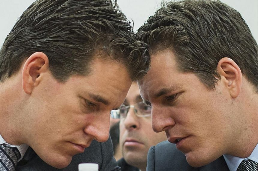 Brothers Cameron (left) and Tyler Winklevoss talk to each other as they attend a New York State Department of Financial Services (DFS) virtual currency hearing in New York in on Jan 28, 2014. The Winklevoss brothers said on March 5, 2014 they had use