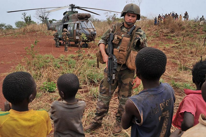 A French soldier stands guard in front of a helicopter transporting French army general Francesco Soriano (unseen), the commander of the French-led Operation Sangaris in Central Africa, during a visit in the town of Yaloke, north of Bangui, on Feb 2,