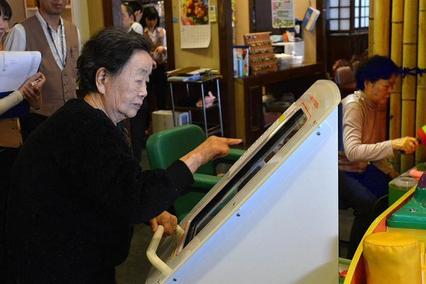 This picture taken on February 7, 2014 shows elderly women playing games at Kaikaya Ltd., a nursing home for the elderly, in Yokohama, suburban Tokyo. The nursing home is run by an offshoot of Namco Bandai, the company behind 1980s arcade phenomenon
