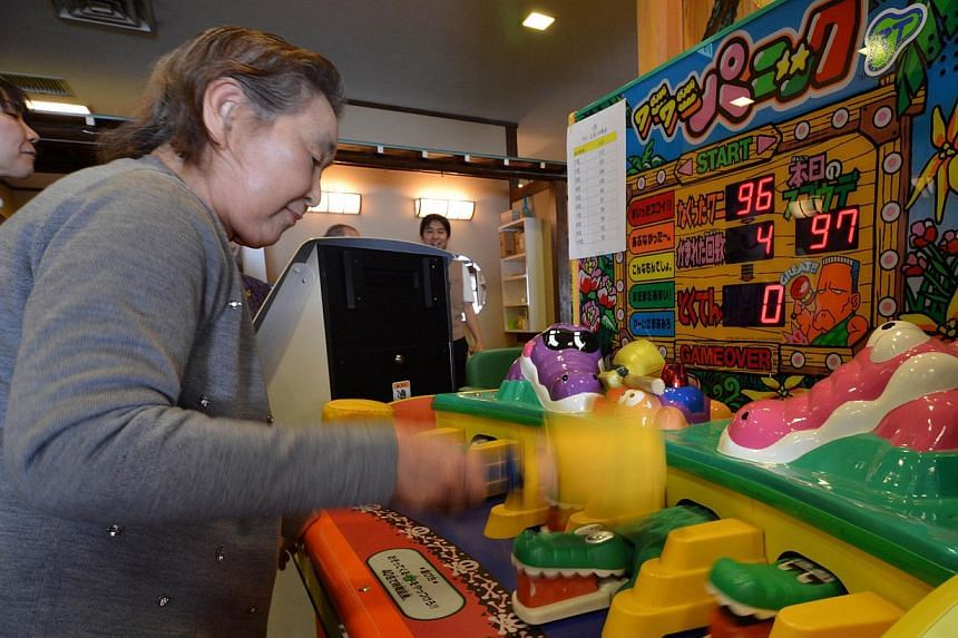 This picture taken on February 7, 2014 shows elderly women playing a game at Kaikaya Ltd., a nursing home for the elderly, in Yokohama, suburban Tokyo. The nursing home is run by an offshoot of Namco Bandai, the company behind 1980s arcade phenomenon