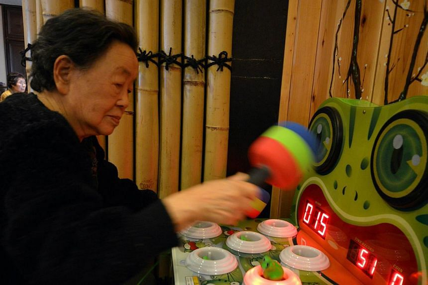 This picture taken on February 7, 2014 shows an elderly woman playing a game at Kaikaya Ltd., a nursing home for the elderly, in Yokohama, suburban Tokyo. The nursing home is run by an offshoot of Namco Bandai, the company behind 1980s arcade phenome